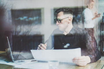 Bearded adult businessman working on modern urban cafe. Photo trough window. Man wearing black shirt and looking laptop, holding papers pencil. Horizontal, film effect, bokeh.