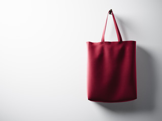 Photo red cotton textile bag hanging right side. Empty white wall background. Highly detailed texture, space for advertising. Horizontal. 3d render