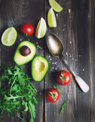 Wall Mural - Fresh avocado, lime, tomatoes and arugula with old spoon