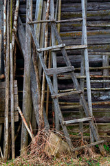 two old ladder against a wall among other wooden objects