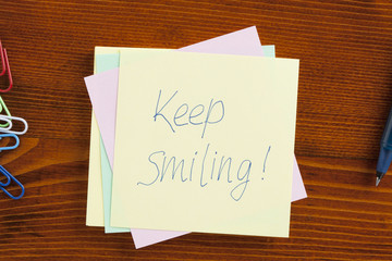 Keep smiling written on a note