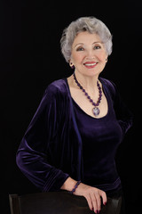 Older woman posing with amethyst jewelry
