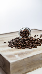 Coffee beans in a glass bottle on wood background