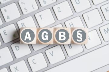 Würfel mit Abkürzung AGB und Paragraph Symbol auf einer Tastatur