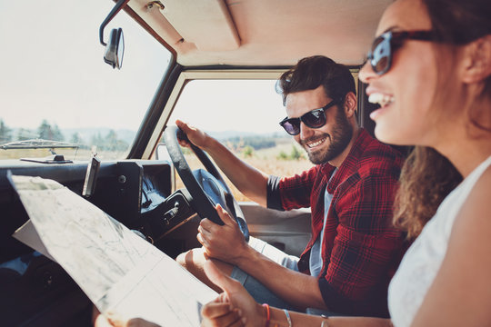 Happy young couple with a map in the car