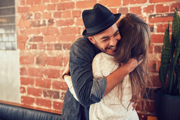 Young man hugging a woman in a coffee shop Wall mural