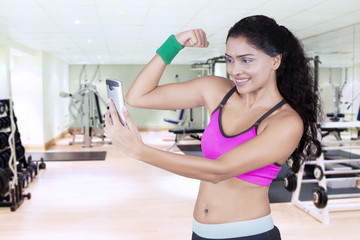 Sporty woman taking selfie photo at gym
