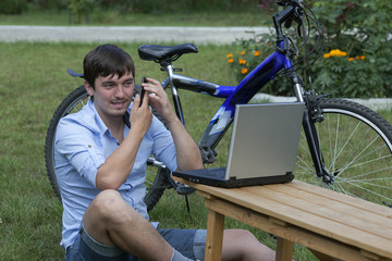 Creative young man with a laptop and a bicycle.