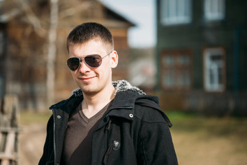 Young Handsome Man Staying Near Old Wooden House In Sunny Day