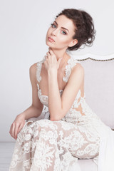 Portrait of beautiful young bride in a luxurious lace wedding dress. She sits on a white vintage sofa. She is an elegant and slim, she has tannes skin, dark hair and gray eyes