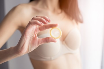 Woman in underwear is holding a condom for a safe sex.