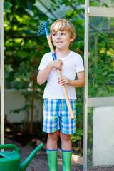 little kid boy working with garden hoe in greenhouse