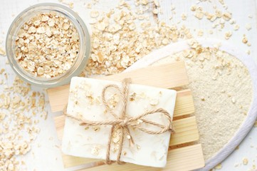 Oatmeal flakes skin care treatment. Rolled oats scattered, body scrubber, handmade soap bar.