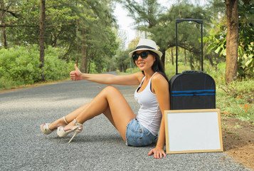 Travel concept. Beautiful woman who is doing the auto-stop along the road with white desk for your text
