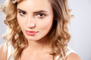 Close-up portrait of beautiful young woman with gorgeous hair and natural makeup. Fashion beauty photo