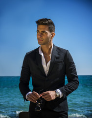 Handsome man in classical suit on beach