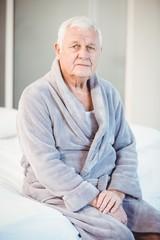 Portrait of suffering senior man sitting on bed