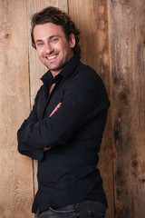 Cheerful handsome man in black shirt standing with arms crossed