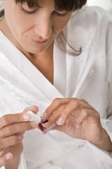 femme qui pose du vernis transparent sur ses ongles de mains