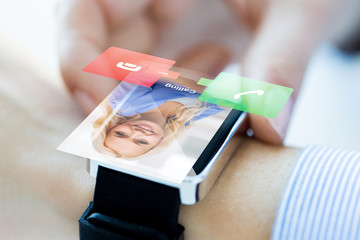 close up of hand with incoming call on smart watch
