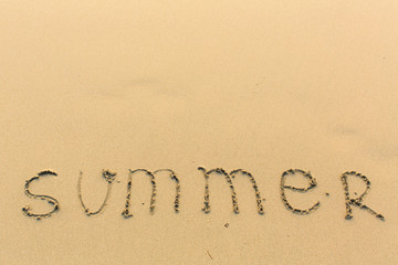 Summer - word drawn on a light wet sand of the sea beach.