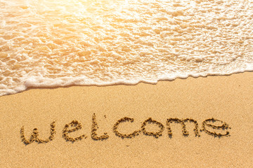 Welcome - drawn on beach sand, soft wave with solar flares.