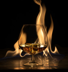 A glass of brandy and ice, on a background of fire
