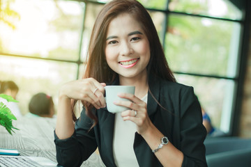 Asian business woman is working and drinking coffee,soft focus
