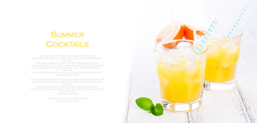 Summer yellow orange lemonade with ice and blood oranges and straw on a wooden table on a white background with place for text, copy space, horizontal, closeup