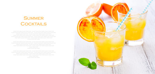 Summer yellow orange lemonade with ice and peaces of blood oranges and straw on a wooden table on a white background with place for text, copy space, horizontal, closeup