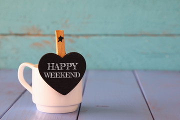 cup of coffee and little heart shape chalkboard with the phrase: HAPPY WEEKEND.