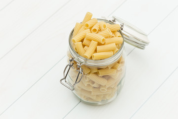 Raw tortiglioni pasta on a glass jar