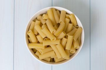Raw tortiglioni pasta in a white bowl