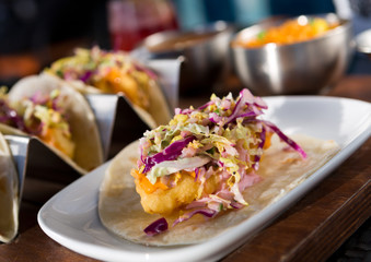 Mexican fried cod fish taco served with lettuce, red onion and sauce