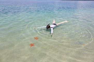 Woman snorkeling in transparent sea above starfish, Panama