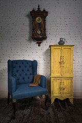 Still life of vintage blue armchair, yellow cupboard, pendulum clock and orange ornate scarf in studio