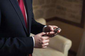 Elegant businessman correcting his clocks and cufflinks