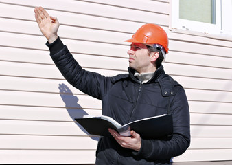 Worker on a construction site in winter looks at the drawing and manages gesticulating