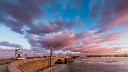 Russia, Saint-Petersburg, 19 March 2016: Pink clouds over the Troitsky Bridge at sunset, drifting ice, frozen Neva River, the traffic on the bridge, a pedestrian walk, Troitskiy