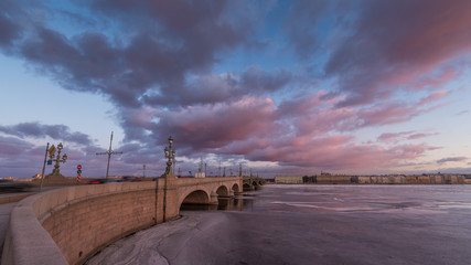 Russia, Saint-Petersburg, 19 March 2016: Pink clouds over the Troitsky Bridge at sunset, drifting ice, frozen Neva River, the traffic on the bridge, a pedestrian walk, Troitskiy