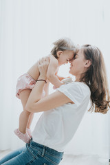 Beautiful mother portrait playing with her cute little girl in a white room in the morning