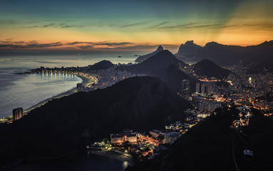 Sunset behind the mountains with iluminated Rio de Janeiro and Copacabana Beach