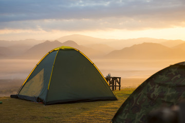Tourist tent on green meadow at sunrise time