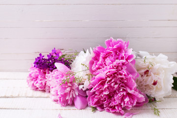 White and  pink peonies flowers on white painted wooden backgrou