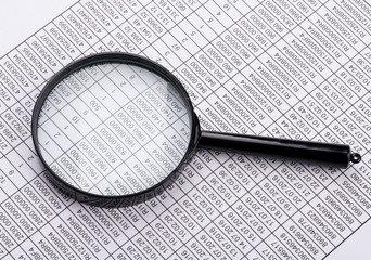 Magnifying glass lies on the statement printed paper
