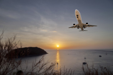 Airplane flying tropical sea at sunset time with reflection