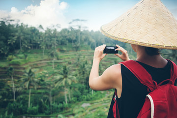 Young lady with traditional Asian hat and backpack making a mobile photo of green tea plants