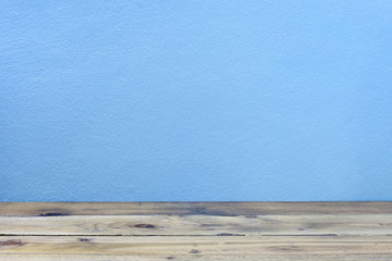 Old wood floor on blue wall background.