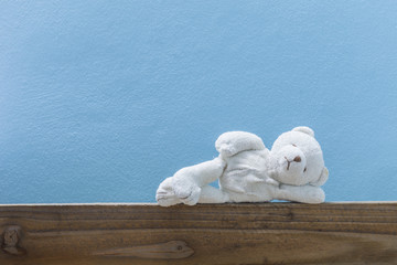 teddy bear sleep ,on old wood  and blue wall background.