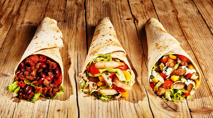 Three meat burritos on table